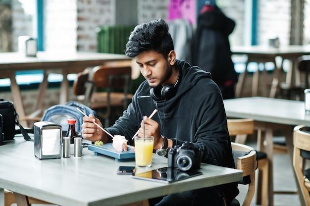카페 먹는 초밥에서 이어폰 캐주얼 하 고 세련 된 젊은 아시아 남자 프리미엄 사진