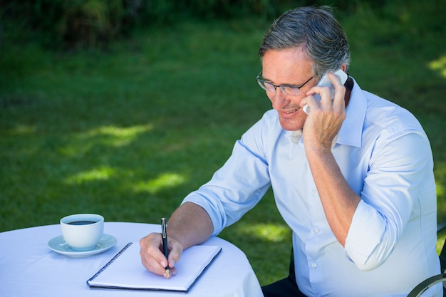 Casual businessman taking notes and having a phone call Premium Photo