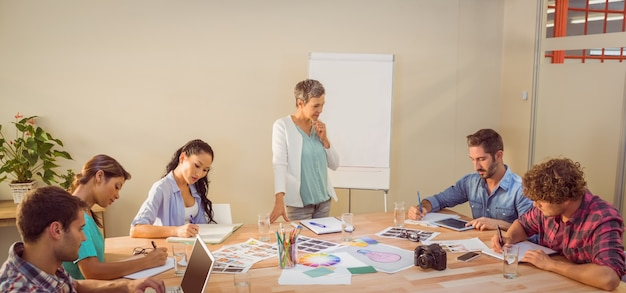 Casual businesswoman giving presentation to her colleagues Premium Photo