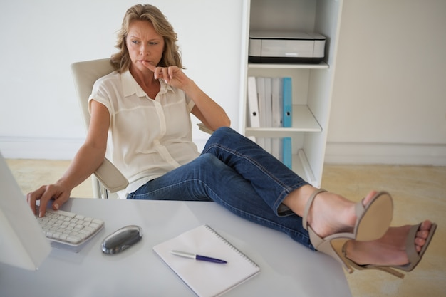 Casual businesswoman working with her feet up at desk Premium Photo