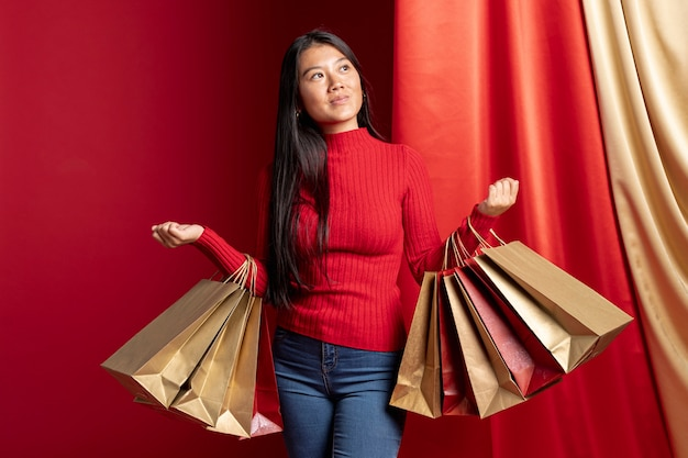 Casual dressed woman holding shopping bags for chinese new year Free Photo