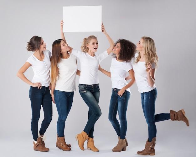 彼らの頭の上に空のホワイトボードを持つカジュアルな女の子 無料写真