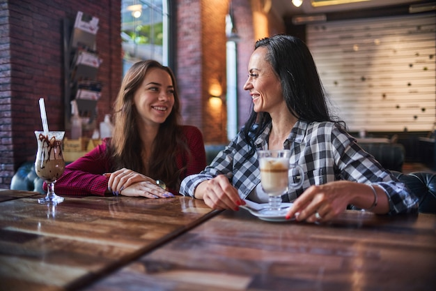 Случайные счастливые улыбающиеся современные мать и дочь вместе проводят кофе-брейк и наслаждаются разговором друг с другом в кафе Premium Фотографии