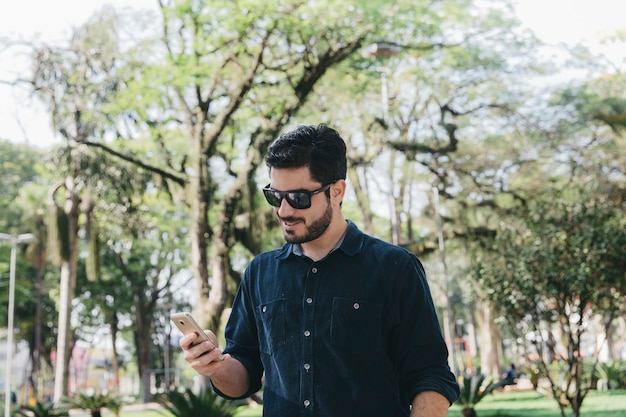 Casual man using phone in park Free Photo