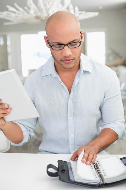 Случайный человек с цифровым планшетом и дневником у себя дома Premium Фотографии