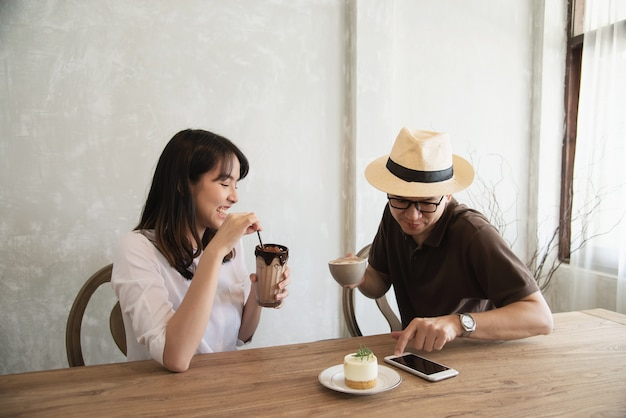 Casual man and woman talking happily while drink coffee and looking mobile phone Free Photo