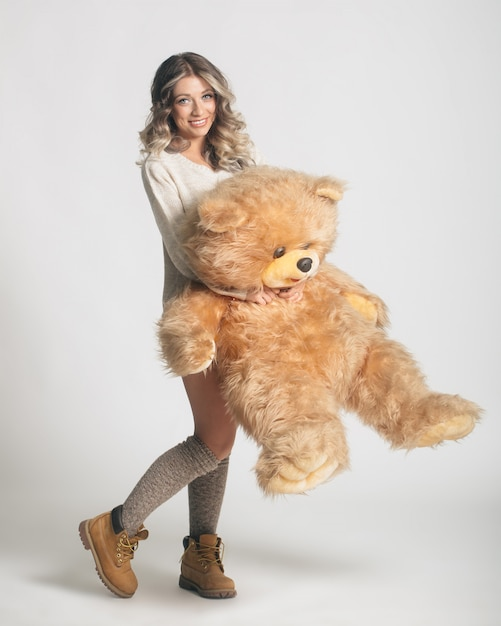 Casual smiling young woman in knitted clothes holding big soft teddy bear Free Photo