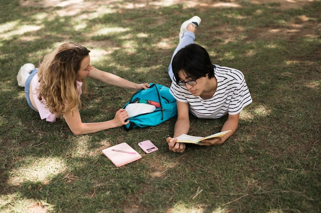 Casual teen students on green meadow in park Free Photo