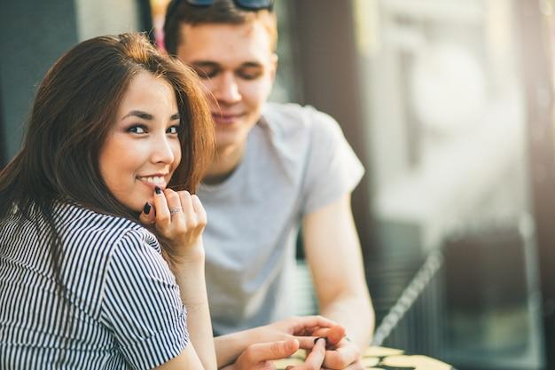 Счастливая молодая пара в любви подростков друзей, одетых в стиле casual, сидя вместе Premium Фотографии