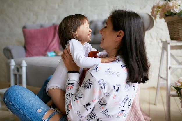 Маленькая девочка и ее мама, одетая в стиле casual, весело играют на полу Бесплатные Фотографии