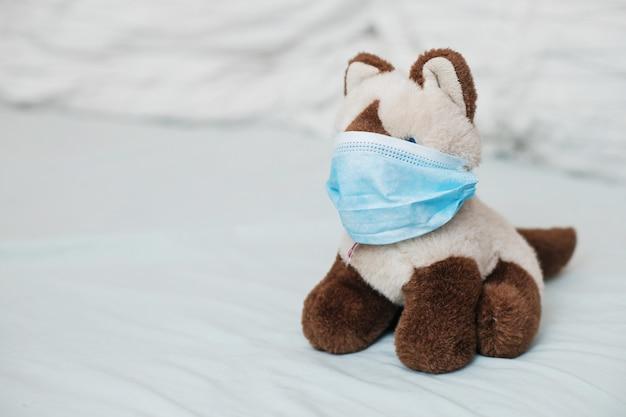 Cat siamese with medical masks on bed. sicker disease in children. coronovirus, quarantine, epidemic, pandemic, cold,illness. medicine concept and health. Premium Photo