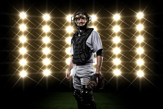 Catcher player in front of lights. Free Photo
