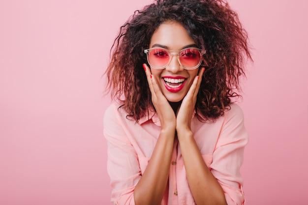 トレンディなサングラスでカーリーガールを捕まえ、身も凍るように笑う。驚いた顔でポーズをとるピンクの綿の服を着た愛らしい黒髪の女性。 無料写真