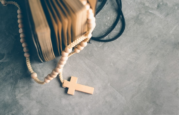 Catholic rosary beads with old book on cement table prayer, rosary background concept in vintage tone. Premium Photo