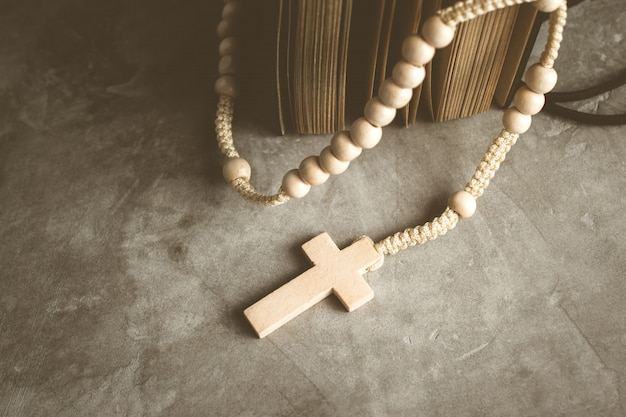 Catholic rosary beads with old book on cement table prayer, rosary background  in vintage tone. Premium Photo