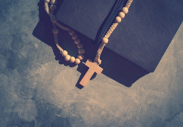 Catholic rosary beads with old book on cement table prayer, rosary background Premium Photo