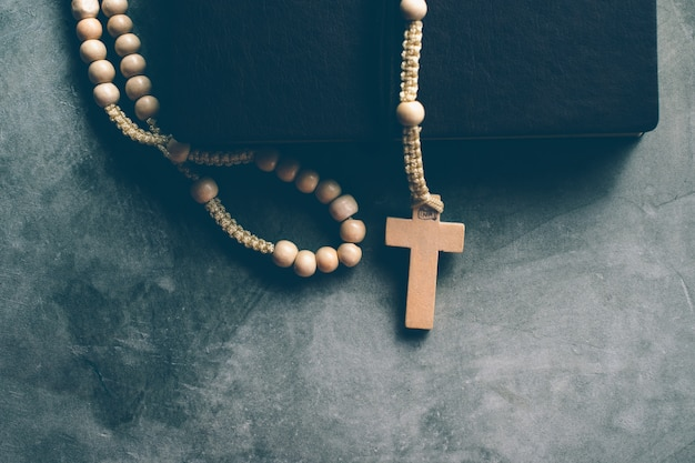 Catholic rosary beads with old book on cement table prayer, rosary Premium Photo