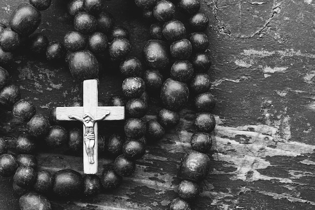 Catholic rosary prayer with a cross on old black wooden  with space for text. close up, top view. black and white toned Premium Photo