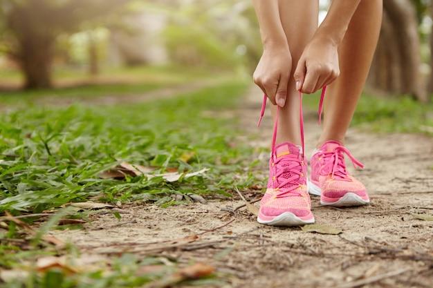 Кавказская спортивная женщина связывает шнурки на розовых кроссовках перед бегом, стоя на тропинке в лесу. женщина-бегун зашнуровывает кроссовки во время тренировки в сельской местности. Бесплатные Фотографии