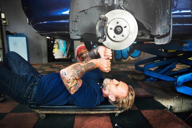 Caucasian auto mechanic man lying reparing car disc brake in garage Free Photo