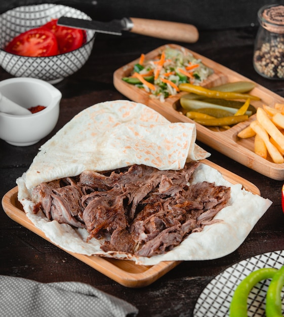 Caucasian barbecue kebab in lavash with french fries and pickles. Free Photo