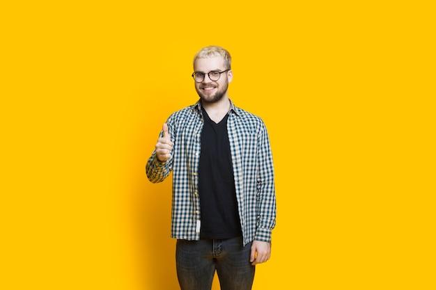 Кавказский бородатый мужчина в очках и светлых волосах жестикулирует на желтой стене в знак одобрения Premium Фотографии