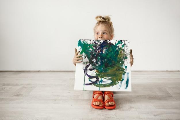 Ragazza prescolare bionda caucasica che mostra immagine che ha dipinto. adorabile bambino con tela. concetto di infanzia felice. Foto Gratuite