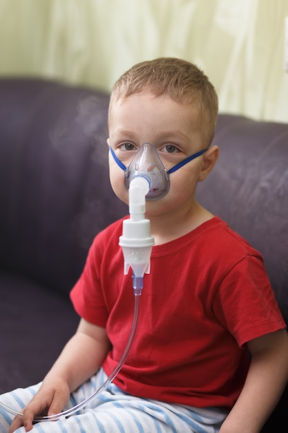Caucasian boy inhales couples containing medication to stop coughing. Premium Photo