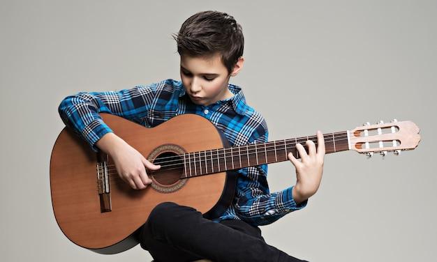 Кавказский мальчик играет на акустической гитаре. Бесплатные Фотографии