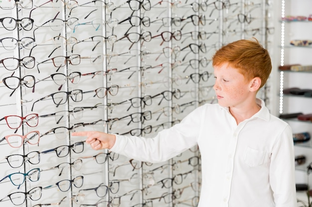 Caucasian boy pointing index finger at eyeglasses rack Free Photo