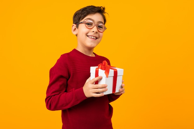 Caucasian boy in a red jumper with a gift box on yellow with copy space Premium Photo