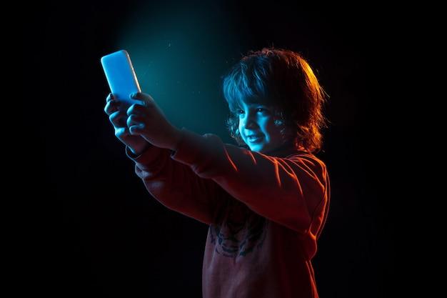 Ritratto di ragazzo caucasico isolato su sfondo scuro studio in luce al neon Foto Gratuite
