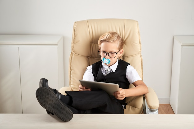 Caucasian boy sitting in executive chair in office with dummy in mouth and using tablet Free Photo