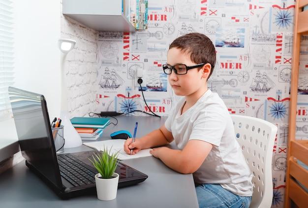 オンライン学習ホームスクーリングにデスクトップコンピューターを使用して白人の少年 Premium写真