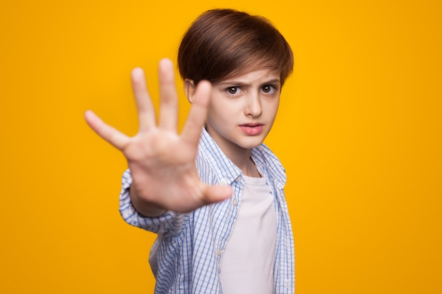 Caucasian boy with ginger hair gesturing the stop sign with palm on a yellow  wall Premium Photo