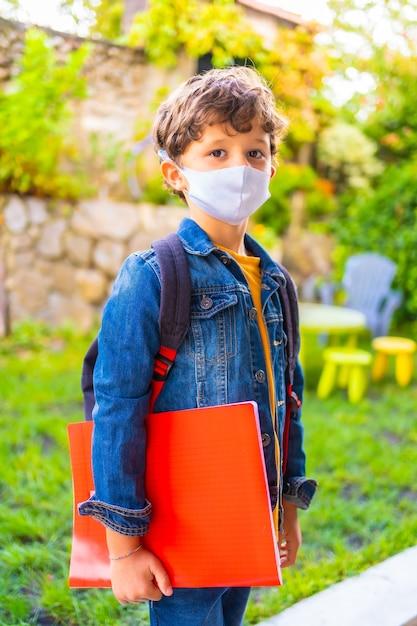 学校に戻る準備ができてフェイスマスクを持つ白人の子。新しい正常性、社会的距離、コロナウイルスのパンデミック、covid-19。ジャケット、バックパック、手元のメモ用の赤いブロック Premium写真