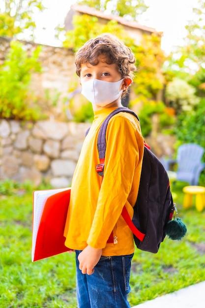 学校に戻る準備ができてフェイスマスクを持つ白人の子。新しい正常性、社会的距離、コロナウイルスのパンデミック、covid-19。オレンジ色のtシャツ、バックパック、メモ帳を手に Premium写真