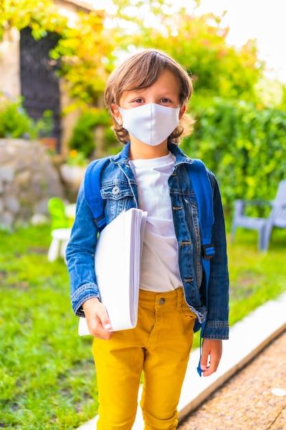 学校に戻る準備ができてフェイスマスクを持つ白人の子。新しい正常性、社会的距離、コロナウイルスのパンデミック、covid-19。デニムジャケット、バックパック、メモ帳を手に Premium写真