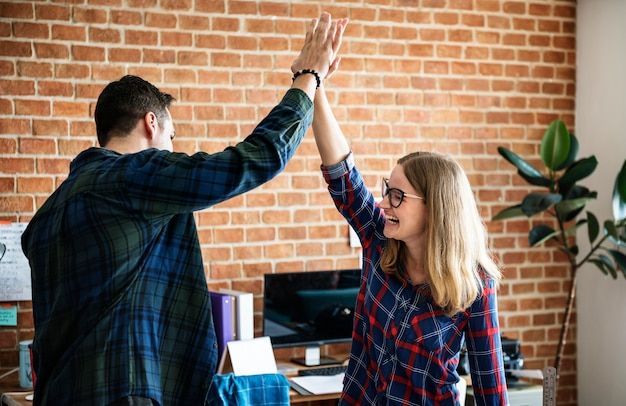 Caucasian colleagues give each other high five Premium Photo