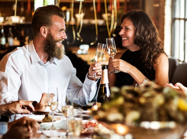 Caucasian couple clinking glasses together at restaurant Free Photo