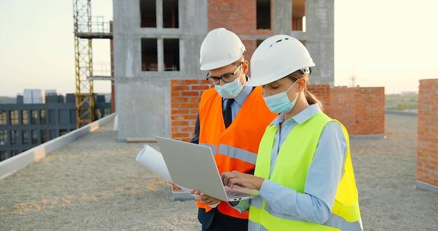 헬멧 및 의료 마스크에 남성과 여성 생성자의 백인 부부는 이야기하고 측면 건물 계획 초안을 논의. 노트북 컴퓨터와 건설에서 일하는 남자와 여자 빌더. 프리미엄 사진