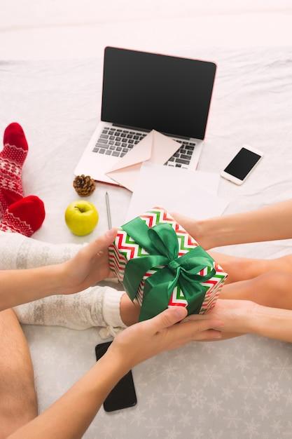 Кавказская пара с подарком. ноутбук и телефон для людей, сидящих на полу в цветных носках. рождество, любовь, концепция образа жизни Бесплатные Фотографии