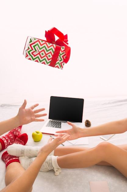 Coppia caucasica con regalo. laptop e telefono per le persone sedute sul pavimento a calzini colorati. natale, amore, concetto di stile di vita Foto Gratuite