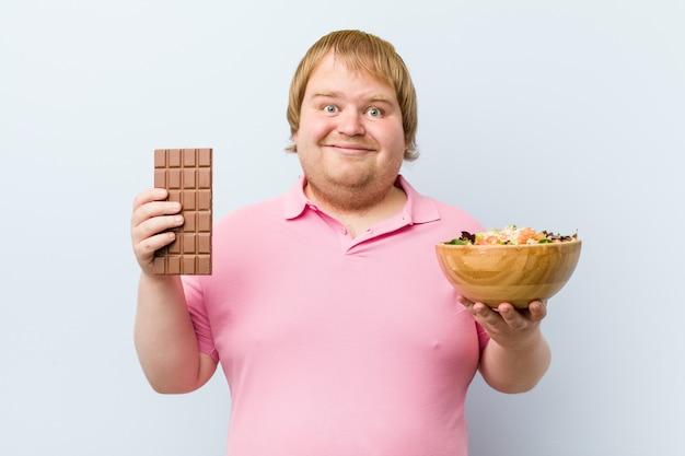 Caucasian crazy blond fat man choosing between chocolate tablet or salad bowl Premium Photo