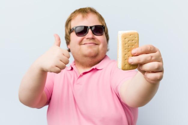 Кавказский сумасшедший блондин толстый мужчина держит мороженое Premium Фотографии