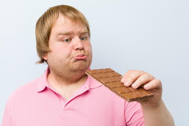 Caucasian crazy blond fat man holding a chocolate tablet Premium Photo