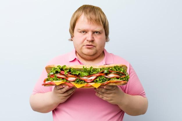 Caucasian crazy blond fat man holding a giant sandwich Premium Photo