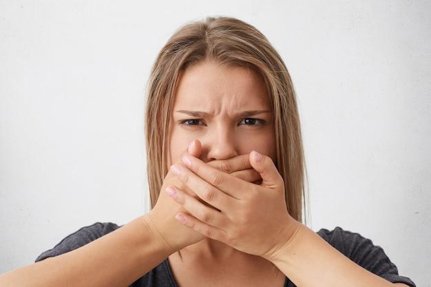 Donna bionda caucasica con sguardo arrabbiato che aggrotta le sopracciglia che copre la bocca con le mani cercando di trattenere la lingua. donna alla moda che cerca di mantenere il silenzio e di non dire il segreto Foto Gratuite