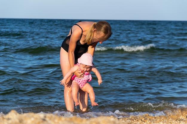 Кавказский ребенок женского пола впервые в море, прыгает в воду и развлекается Premium Фотографии