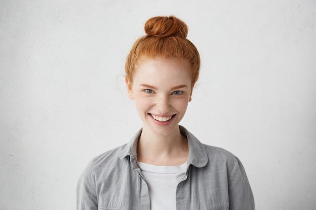 彼女の誠実な笑顔を示す青い魅力的な目で見ている生姜髪のパンを持つ白人女性。嬉しい魅力的な自然な赤毛の女性 無料写真